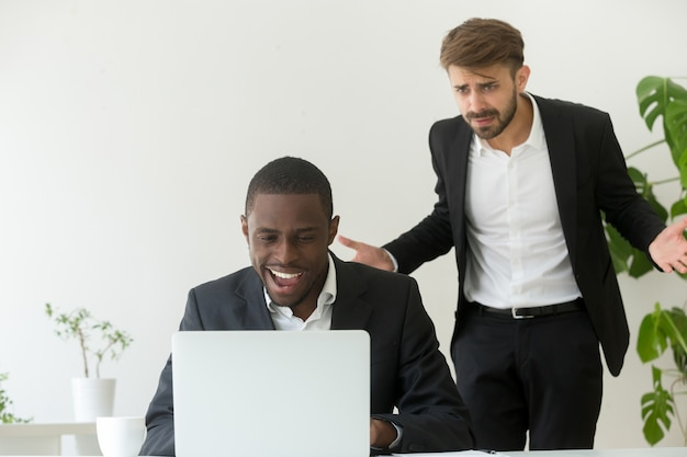 Jefe enojado atrapando empleados africanos entretenidos en línea en lugar de trabajar