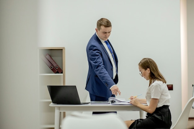 Jefe enojado gritando a su joven empleado, ella está estresada y se siente frustrada: jefe hostil y concepto de acoso.