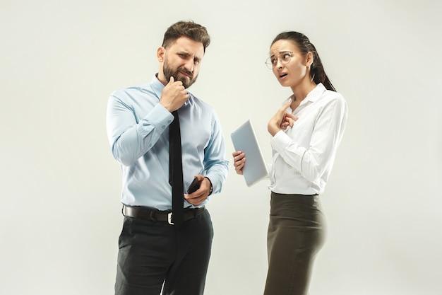 Jefe enojado hombre y su secretaria de pie en la oficina o estudio.