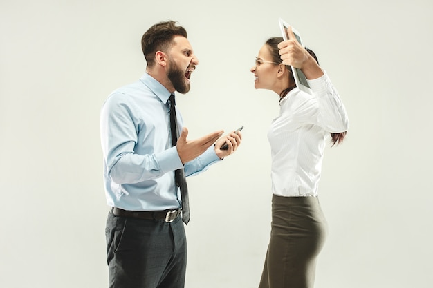 Jefe enojado hombre y su secretaria de pie en la oficina o estudio