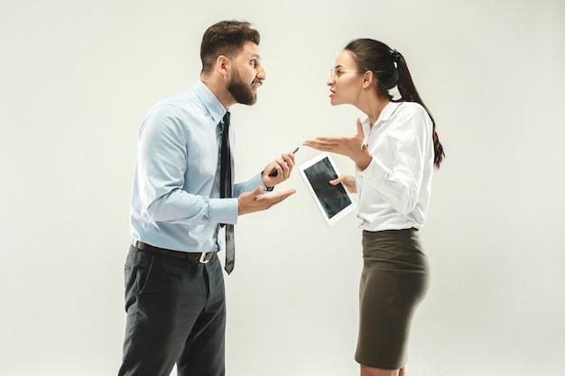 Jefe enojado hombre y su secretaria de pie en la oficina