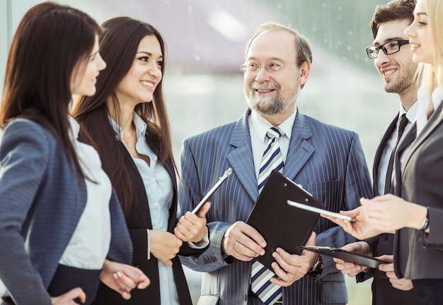 Jefe y equipo empresarial con tableta y documentos de trabajo.