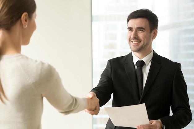 Jefe felicitando a empleada con promoción.