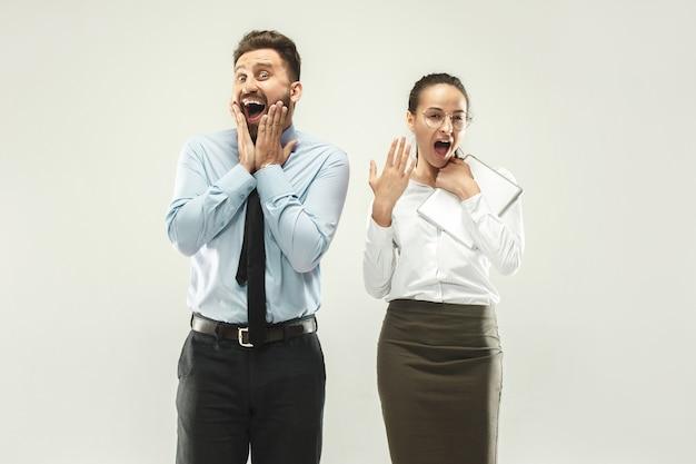 Jefe feliz hombre y su secretaria de pie en la oficina o estudio.