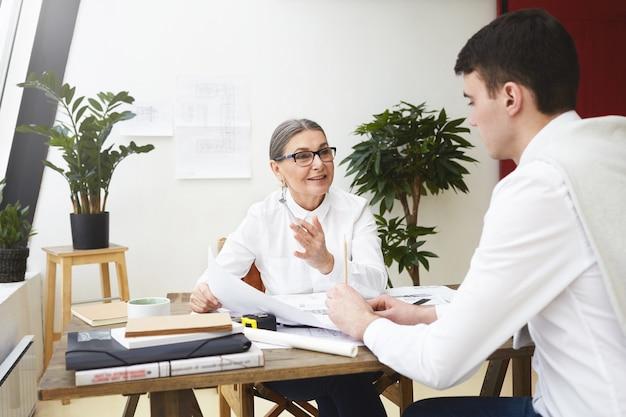 Jefe femenino maduro positivo alegre en gafas con estilo con planos de ingeniería del talentoso arquitecto joven, sonriendo feliz, elogiándolo por su excelente trabajo. trabajo, carrera y éxito