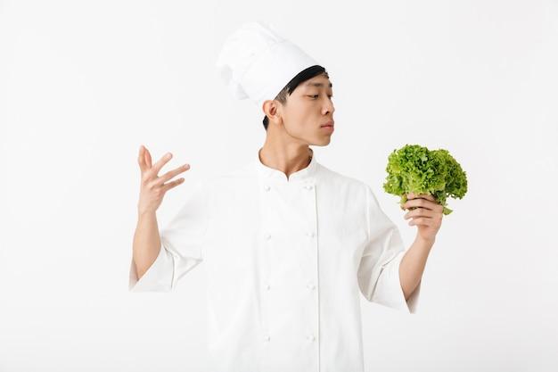 Jefe joven asiático en uniforme de cocinero blanco sonriendo a la cámara mientras sostiene ensalada de lechuga verde aislado sobre la pared blanca
