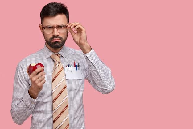 El jefe masculino sombrío serio en ropa formal mantiene la mano en las gafas, muerde la deliciosa manzana roja