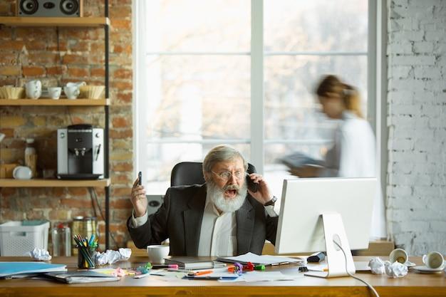 Jefe nervioso y cansado en su lugar de trabajo ocupado mientras la gente moviéndose cerca borrosa. trabajador de oficina, gerente trabajando, tiene problemas y fecha límite, sus colegas distraen. negocio, trabajo, concepto de carga de trabajo.