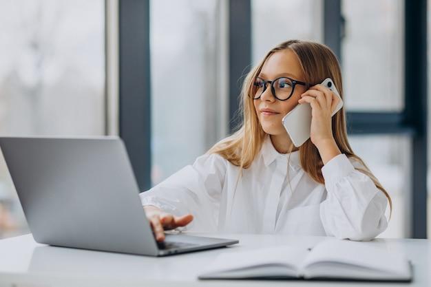 Jefe de niño usando laptop y hablando por teléfono