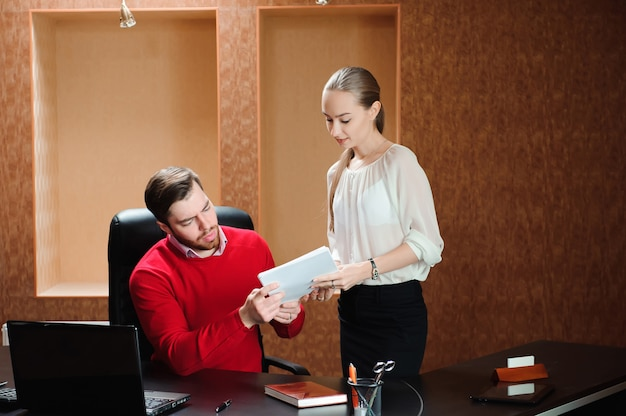 Jefe seguro con papel explicando algo a secretaria