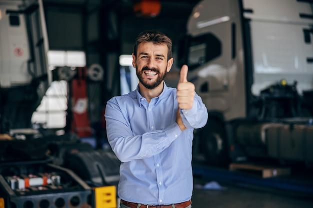 Jefe sonriente de pie en el aparcamiento y mostrando los pulgares para arriba. firma de importación y exportación.
