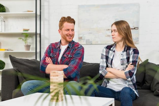 Jenga de madera frente a una joven pareja con el brazo cruzado mirándose