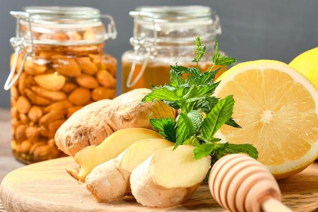 Jengibre, limón y menta en una tabla de madera con miel y nueces.