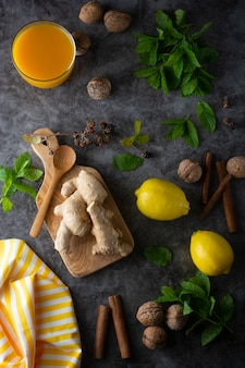 Jengibre, limones y hojas de menta en superficie oscura,