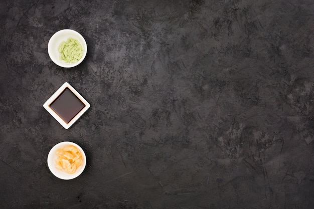 Jengibre marinado salsa de soja y tazón de wasabi dispuestos en fila sobre una superficie texturada negra