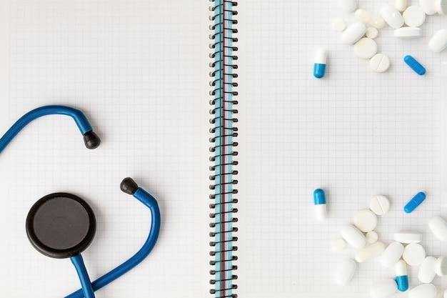 Jeringa, estetoscopio, bloc de notas de página en blanco y píldora sobre la mesa del médico. diagnóstico médico o maqueta de prescripción médica