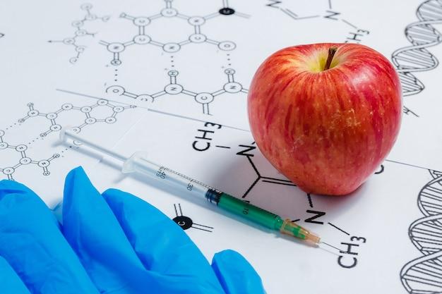 Jeringa, guantes azules y manzana roja sobre fondo blanco con fórmula química,