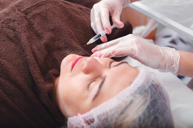 Jeringa de inyección en el rostro de la mujer.