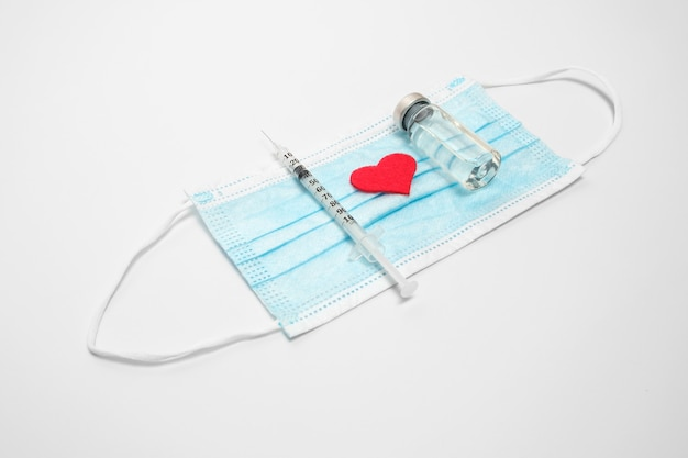 Jeringa de inyección y vacuna contra el virus corona en máscara médica, con corazón rojo.