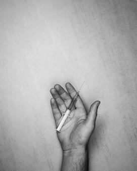 Jeringa médica con aguja y drogas en una palma masculina abierta sobre un fondo gris