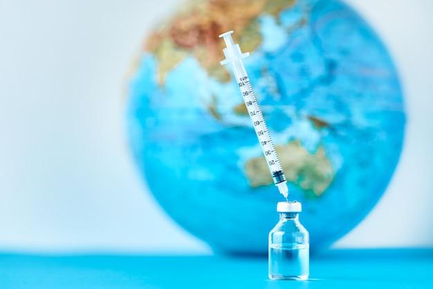 Jeringa médica y ampolla con medicina contra el planeta tierra.