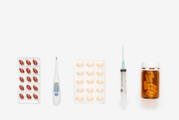 Jeringa médica, termómetro digital y pastillas.