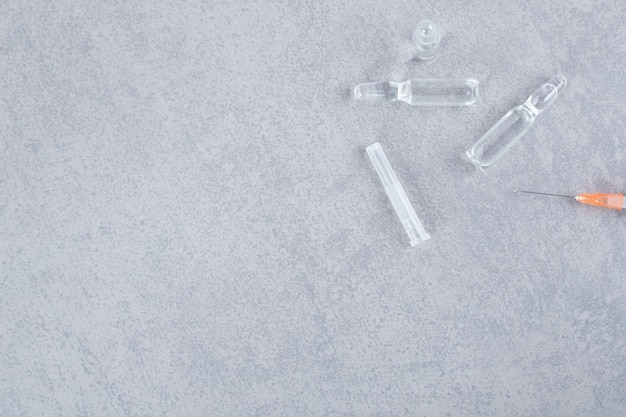 Jeringa vacía con píldoras médicas líquidas sobre superficie gris