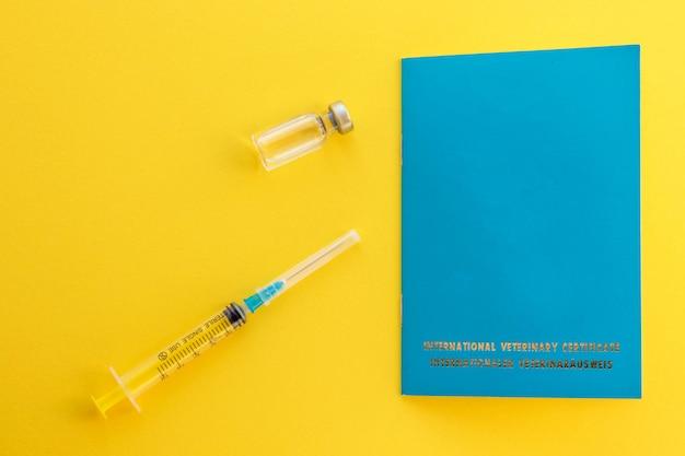 Jeringa, vial de vidrio con pasaporte líquido y animal para indicar vacunas y número de microchip