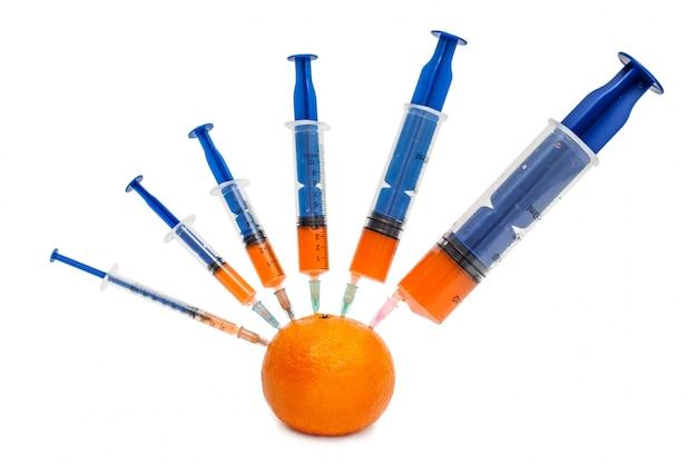 Jeringas de diferentes tamaños, desde pequeñas a grandes, pegadas en mandarina sobre blanco.