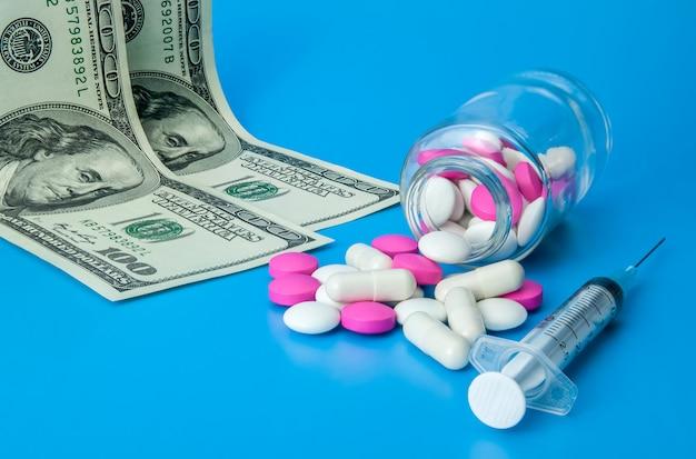 Jeringuilla, dólares y píldoras rosadas y blancas en un fondo azul brillante.