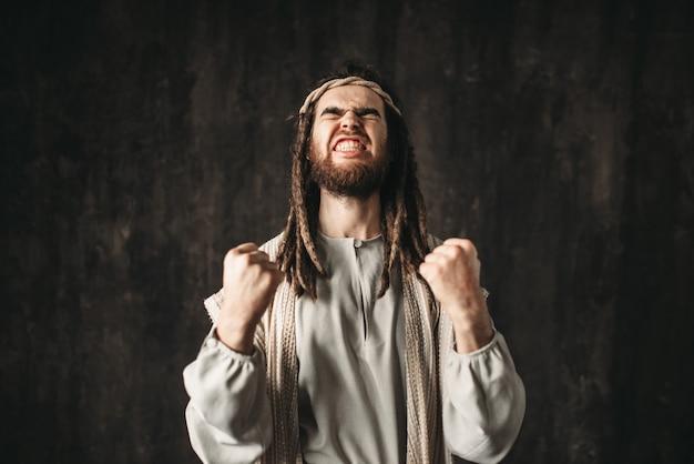 Jesucristo en túnica blanca ora emocionalmente apretando las manos en puños
