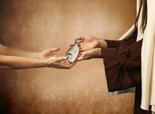 Jesús le da el pescado a un mendigo.