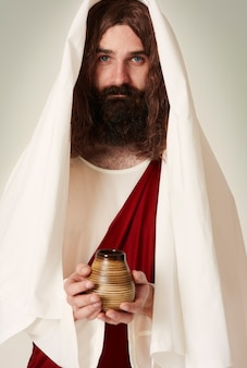 Jesús vistiendo túnica sosteniendo agua bendita en la jarra