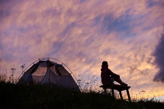 Jiker turístico femenino sentado cerca de su tienda de campaña en la cima de la montaña