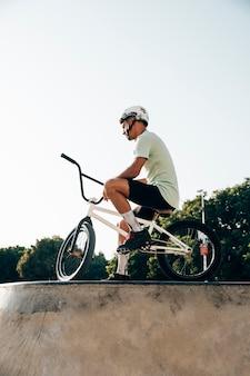 Jinete de bmx adolescente de pie con su bicicleta vista de ángulo bajo
