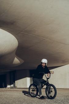 Jinete de bmx mirando a otro lado sentado en su bicicleta con un moderno edificio en segundo plano.