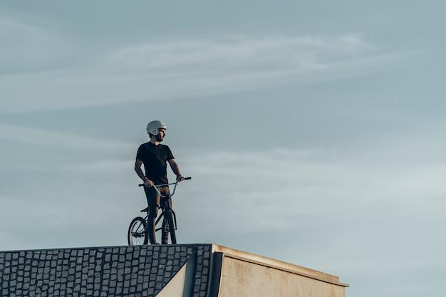Jinete masculino de bmx mirando a otro lado en el parque de bicicletas de ladrillos de piedra