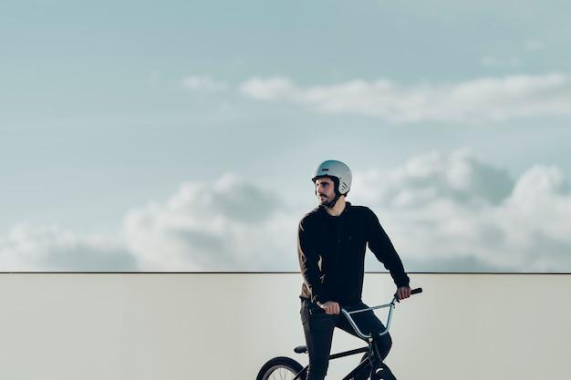 Jinete masculino de bmx que mira lejos con la cerca blanca y el cielo nublado en fondo