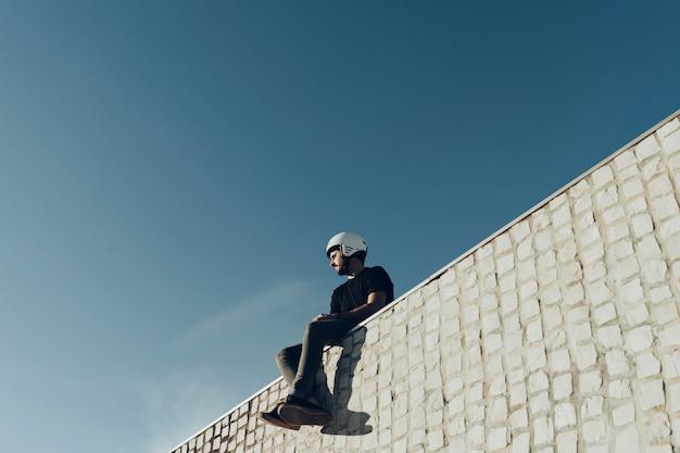 Jinete masculino de bmx sentado en la parte superior del parque de bicicletas mirando a otro lado