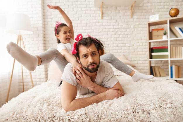 El jinete de niños pequeños está sentado sobre papá