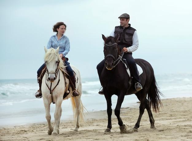 Jinetes y caballos en la playa.