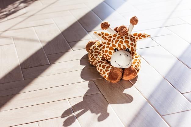 La jirafa de peluche suave para niños se sienta sobre fondo de madera, luz dura y sombra