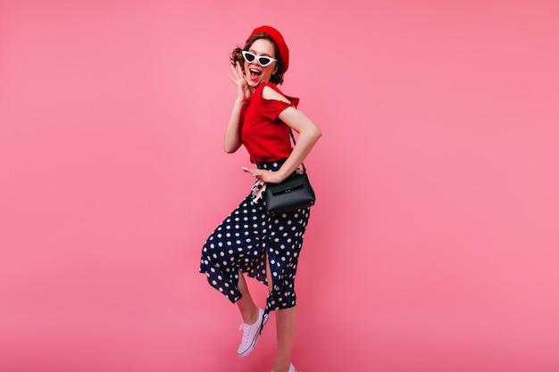 Jocund mujer francesa con gafas de sol expresando felicidad. foto interior de hermosa dama rizada bailando en la pared rosada.