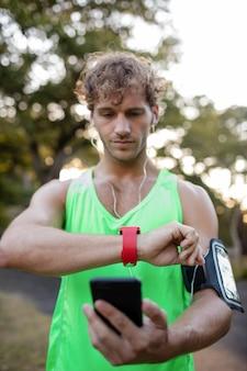 Jogger escuchando música en el teléfono móvil y revisando su reloj inteligente