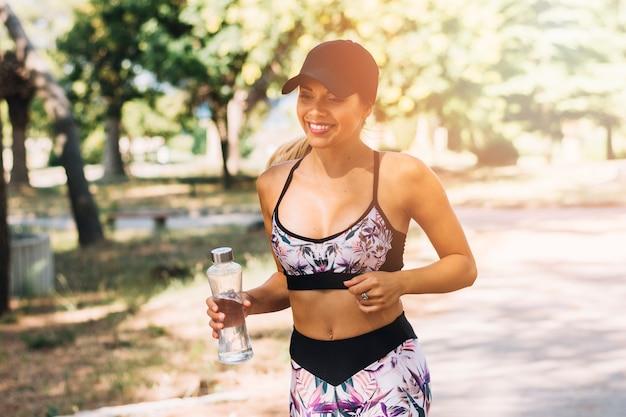 Jogger femenino sonriente que corre con la botella de agua en el parque