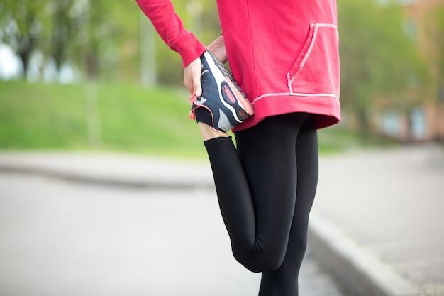 Jogger haciendo estiramientos antes de correr la práctica. de cerca