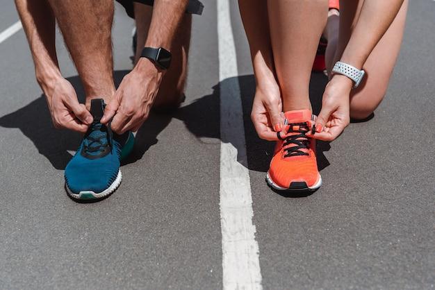 Joggers que atan cordones de zapatos en zapatillas en la pista de atletismo