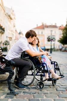 Joven abraza a su mujer en la silla de ruedas desde atrás, mientras está sentado en el banco en la calle de la ciudad vieja