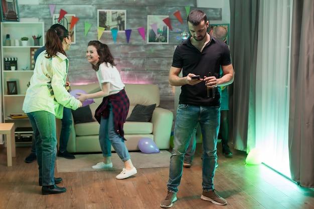 Joven aburrido usando su teléfono inteligente en una fiesta mientras sus amigos bailan.