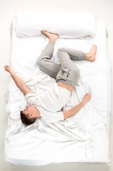 El joven acostado en una cama